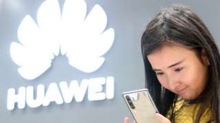 A young woman looking at a Huawei smartphone