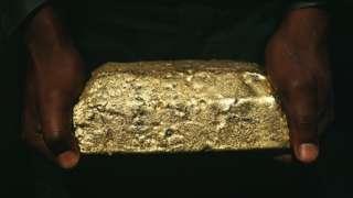 Man holding a gold ingot