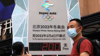 A woman uses her phone in front of a countdown clock showing 200 days to the opening of Beijing 2022 Winter Olympic Games, in Beijing, China July 19, 2021.