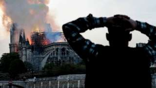 A man watches the landmark Notre-Dame Cathedral burn, engulfed in flames, in central Paris on April 15, 2019