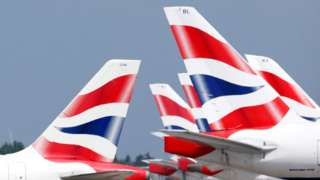 British Airways plane tail fins - which feature the UK flag - are arrayed in rows at an airport