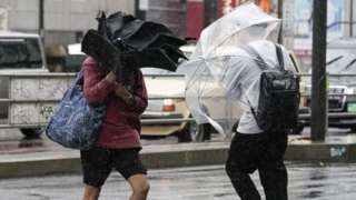 Two pedestrians (not the homeless people in question) brave the storm on Saturday in Tokyo