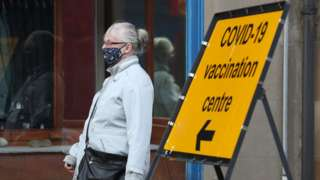 Masked woman walks past Covid sign