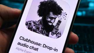A person holding an iPhone with the Clubhouse app open
