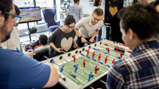 Employees of Smarkets play table football during their lunch break at their office in central London on March 12, 2018