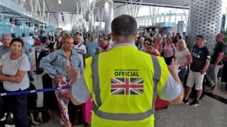 A British government official speaks to tourists, flying with Thomas Cook from Tunisia