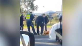 Four police officers stand over the man who is lying on the ground during the arrest