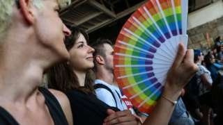 A participant holds a fan with rainbow colours during the lesbian, gay, bisexual and transgender (LGBT) Pride Parade in Budapest on July 24, 2021.