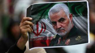 An Iranian holds up a picture of Qasem Soleimani in Tehran, Iran, on 4 January 2020