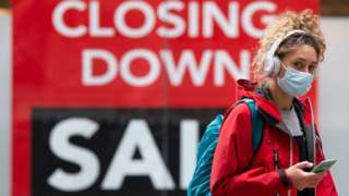 Woman wearing face mask and headphones walks past a closing down sign in a Cardiff shop window