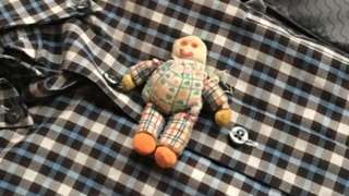 An image of a doll packed in a suitcase on top of a shirt.