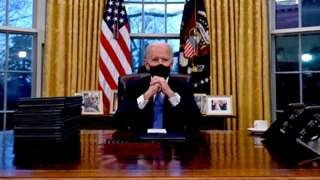 President Biden sits at his desk in the Oval Office