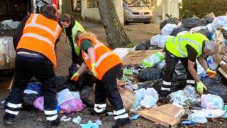Refuse workers clear a street in Brighton