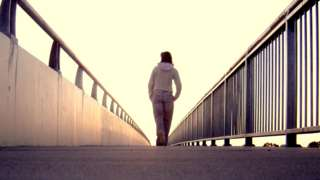 A stock model walks across a bridge with her back to the camera