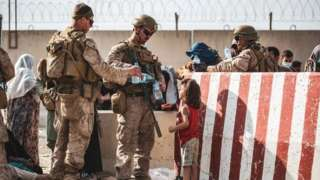 U.S. Marines hand out water during an evacuation at Kabul's airport
