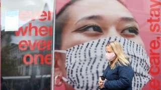 Mulher anda na rua usando máscara em Manchester