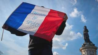 A protester waves a French Tricolor flag with 'Freedom of Speech' written on it during an anti-terrorism vigil on Sunday