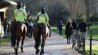 "Police patrol on horseback through St James"" Park in London. Millions more people moved to harsher coronavirus restrictions as the new tier changes came into force in England."