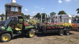 A tractor attached to a cart of flowers