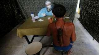 Em tenda de atendimento, homem indígena de costas é atendido, do outro lado da mesa, por profissional de saúde todo coberto por jaleco e face shield