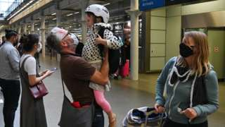 A father greets his daughter after arriving in a Eurostar train from Paris