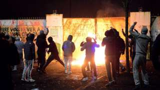 Young people, most with their hoods up, standing in front of an exploding petrol bomb in west Belfast