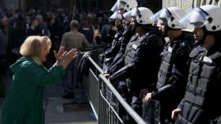 A woman talks to police forces standing guard outside the presidential building in Belgrade