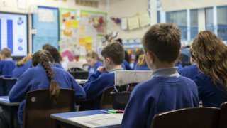 Stock photo of school pupils pictured from behind