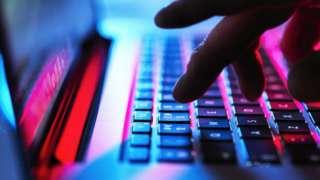 Man typing at his laptop (stock photo)