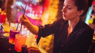 Stock image of a woman making drinks in a bar