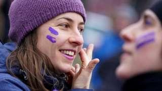 चेहरे पर बेंगनी रंग लगाती हुई एक महिला