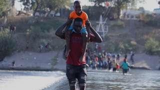 Migrants from Haiti cross the Rio Grande, on the border of Ciudad Acuna, Mexico, 17 September 2021