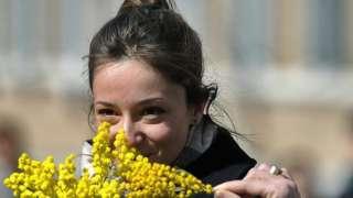 2012లో అంతర్జాతీయ మహిళా దినోత్సవం రోజున మిమోసా పూలగుత్తితో రోమ్ నగరంలో ఒక మహిళ