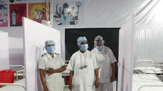 Nurses wear PPE on a ward in India