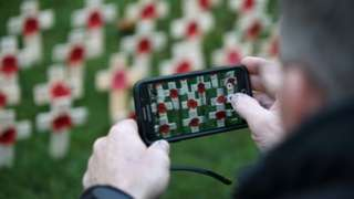 Man takes picture of memorial on phone