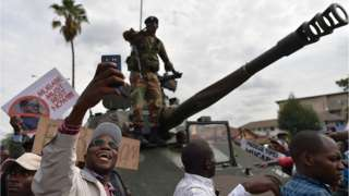 A man takes a selfie of a Zimbabwean Defence Force soldier standing on a tank during a march in the streets of Harare