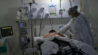 Paciente com sobrepeso e em maca virado de bruços, observado por enfermeira