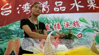 Chinese woman prepares a stand to display Taiwan-grown fruit displayed at the 4th China International Consumer Goods Fair on June 8, 2005 in Ningbo, Zhejiang province, China.