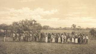 Trabalhadores escravizados perfilados carregando enxadas e cestos para o trabalho no campo, observados por feitor. Litografia de Fréderic Sorrieu sobre foto de Victor Frond