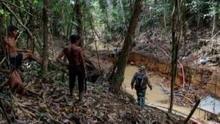 """Yanomami indians follow agents of Brazil""""s environmental agency in a gold mine during an operation against illegal gold mining on indigenous land on 17 April 2016"""