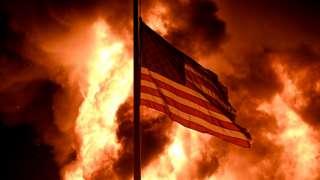 美国威斯康辛州基诺沙市社区矫正大楼前一面美国国旗在示威者纵火点燃的火堆前飘扬(24/8/2020)