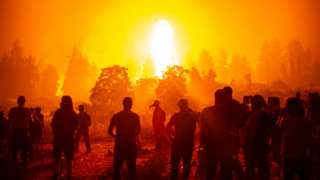 A silhouette of firefighters looking towards a large fire
