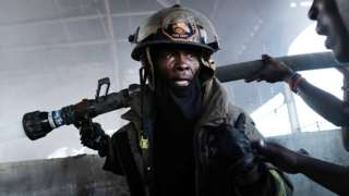 A firefighter tackles the blaze in Port au Prince's Iron Market