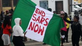 Protesters hold a Nigerian flag with an inscription during a protest against the Nigeria rogue police, otherwise know as Special Anti-Robbery Squad (SARS), in Ikeja district of Lagos, Nigeria, 15 October 2020