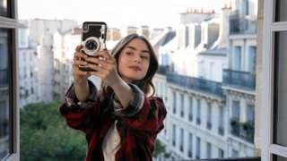 Lily Collins, interpretando Emily, tira selfie de sacada em Paris, com prédios históricos ao fundo