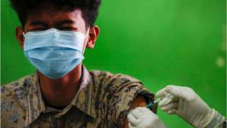 """An Indonesian student reacts as he receives his first dose of China""""s Sinovac Biotech vaccine for the coronavirus disease (COVID-19) at a high school, as the cases surge in Jakarta, Indonesia, 1 July 2021."""