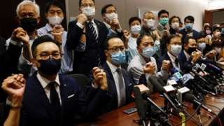Pro-democracy lawmakers hold hands in front of the media as they resign en masse in Hong Kong