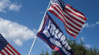 A Trump campaign flag and US flag