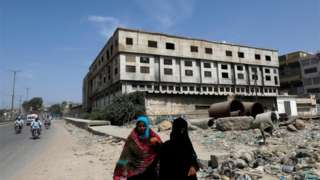 Women walk along a road with an abandoned building of a garment factory in the background, where over 260 people were killed after a fire broke in 2012, in Karachi, Pakistan September 17, 2020.