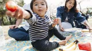Criança oferecendo comida